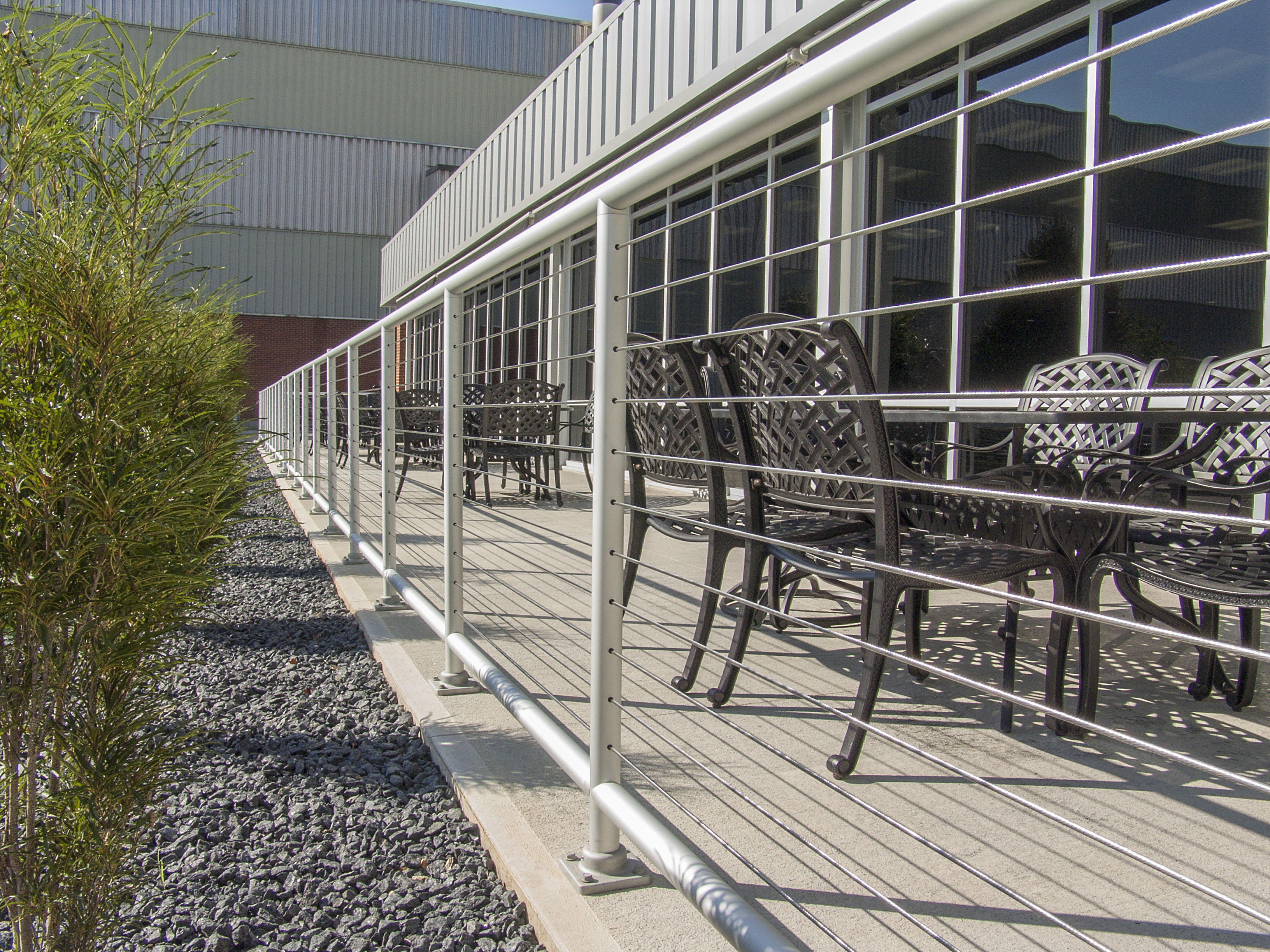 Pipe cable railing borders an outdoor dining space at an Ohio manufacturing facility