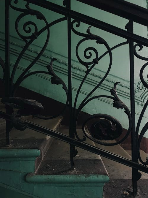 cast iron railing on a stairway with leaf designs.