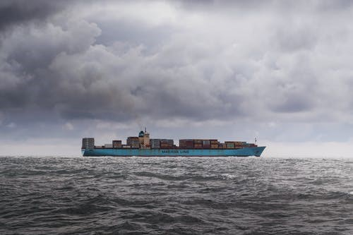 cargo ship in the middle of the ocean during a storm.