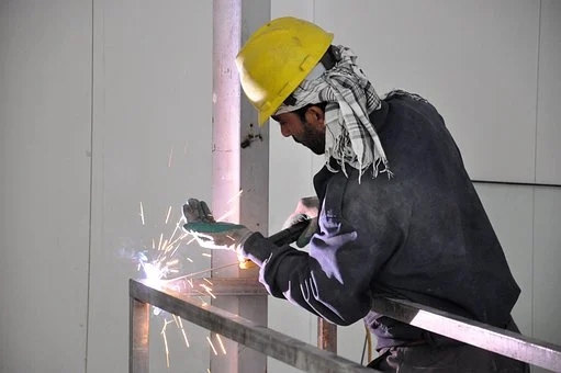 Worker welding together an unassembled railing section.